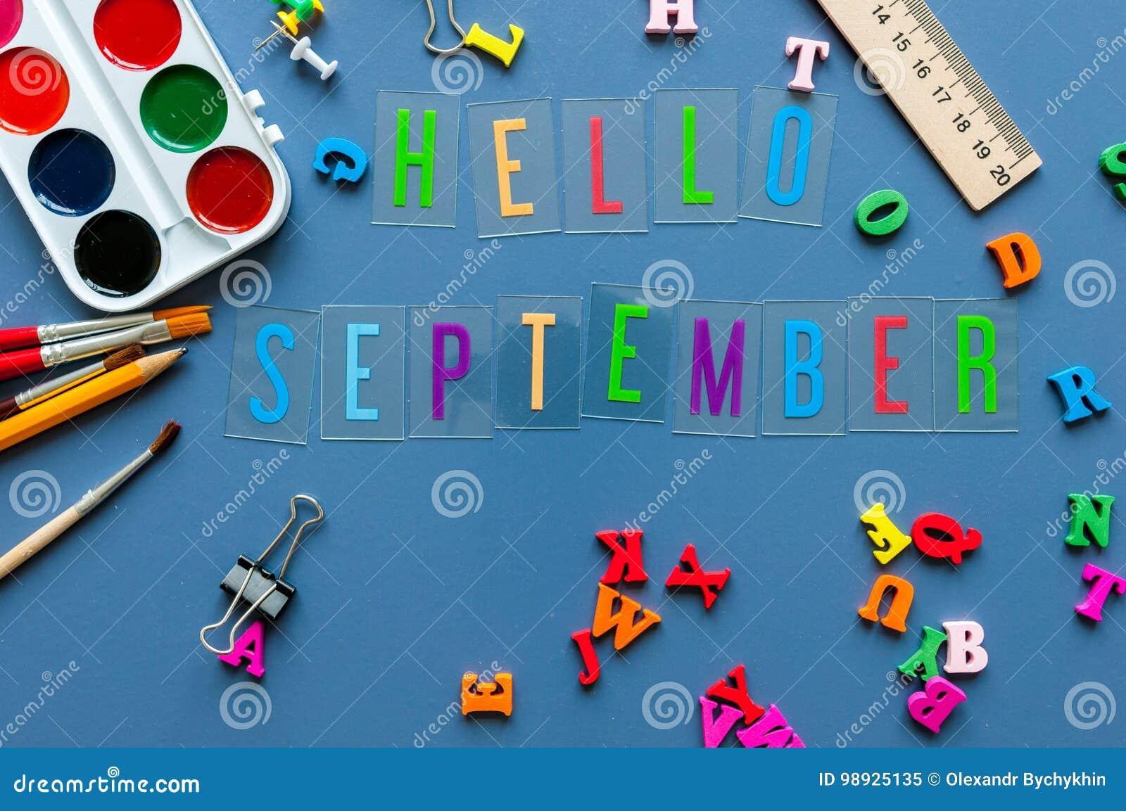 Olá! texto de setembro na tabela do professor ou do aluno com beira do lado de fontes da escola em um fundo azul