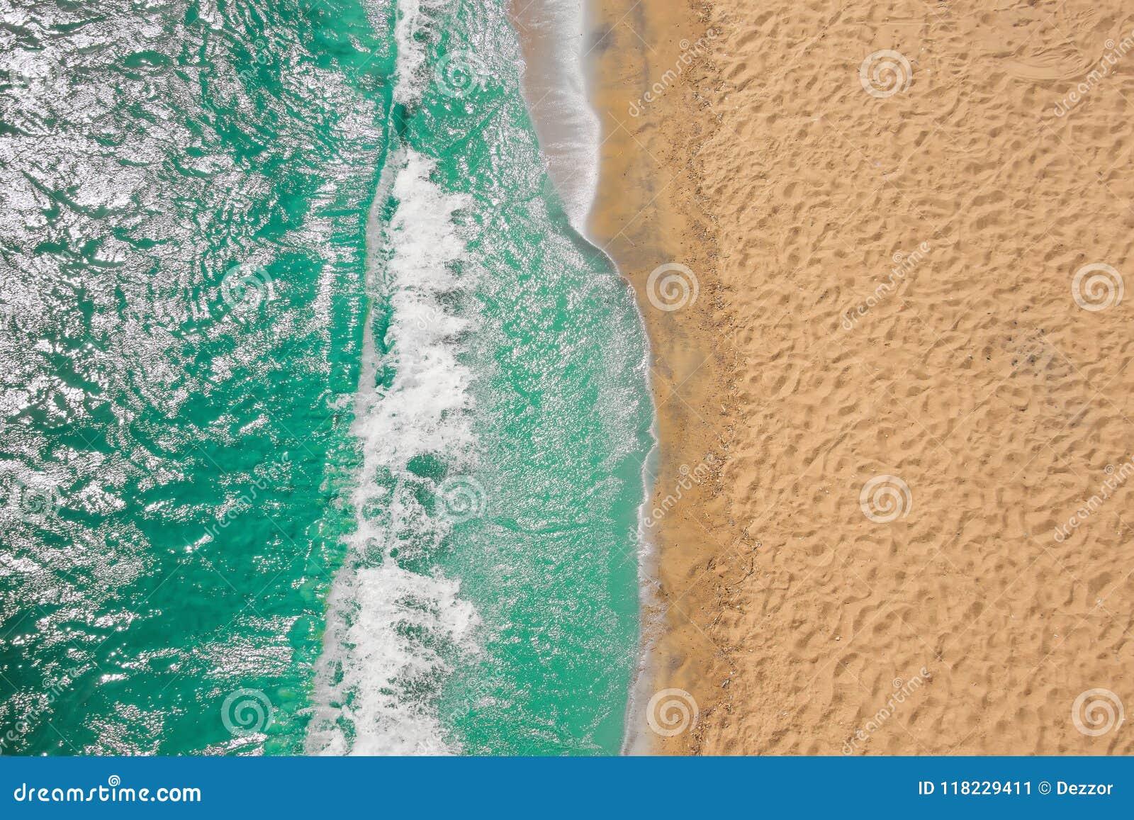 Olas oceánicas de la playa de la costa costa con espuma en la arena Visión superior desde el abejón