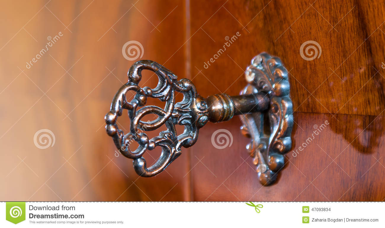 Old antique skeleton key in lock of wooden cabinet - Old Antique Skeleton Key In Lock Of Wooden Cabinet Stock Photo