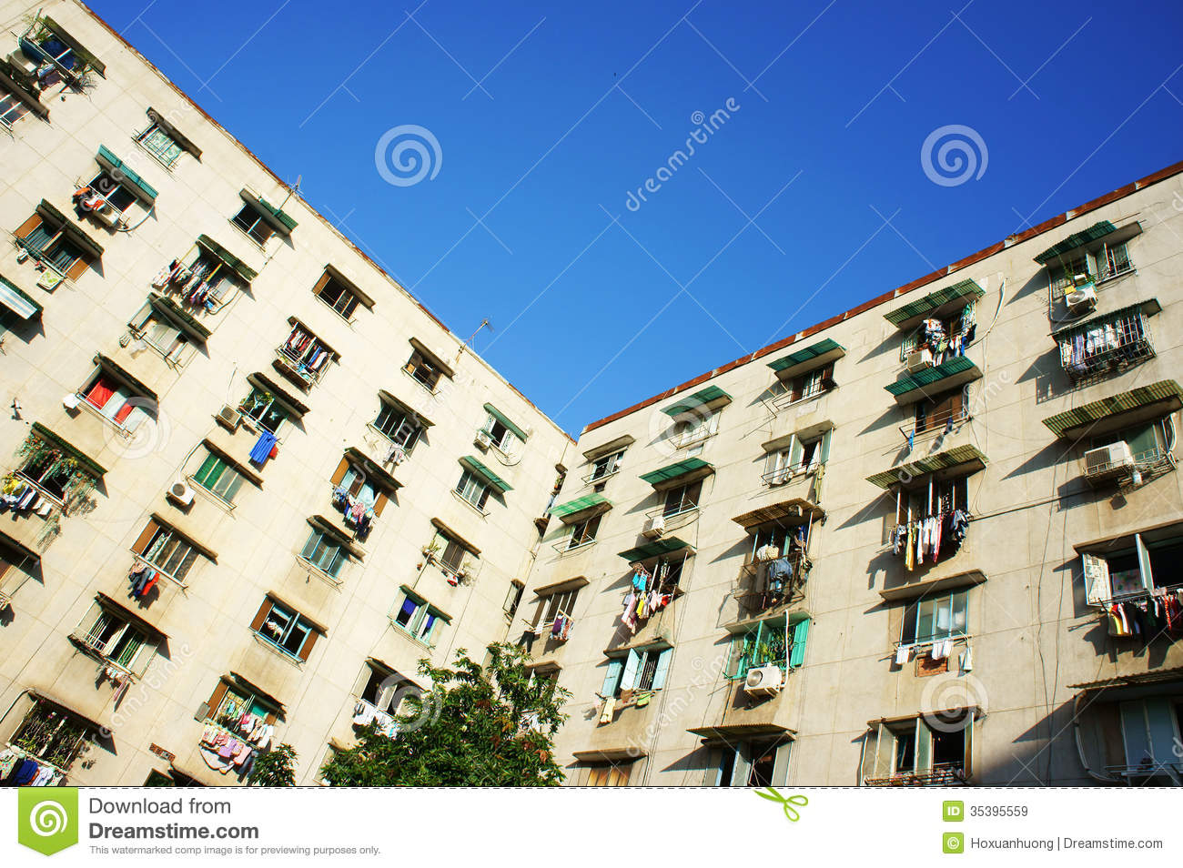 Old apartment building with rows of windows under blue sky