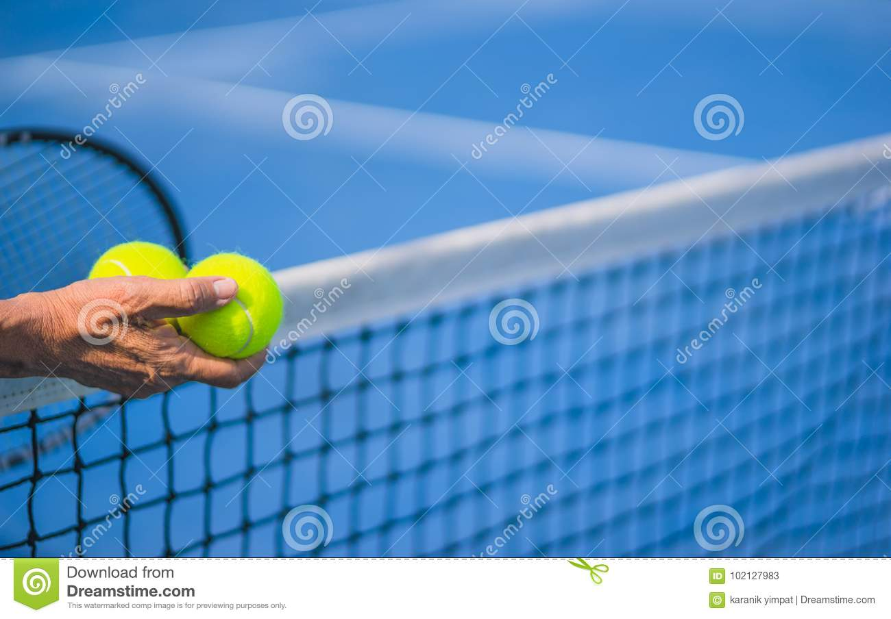 Old asian man hold two tennis balls in right hand, selective focus, blurred racket, net and blue tennis court as background