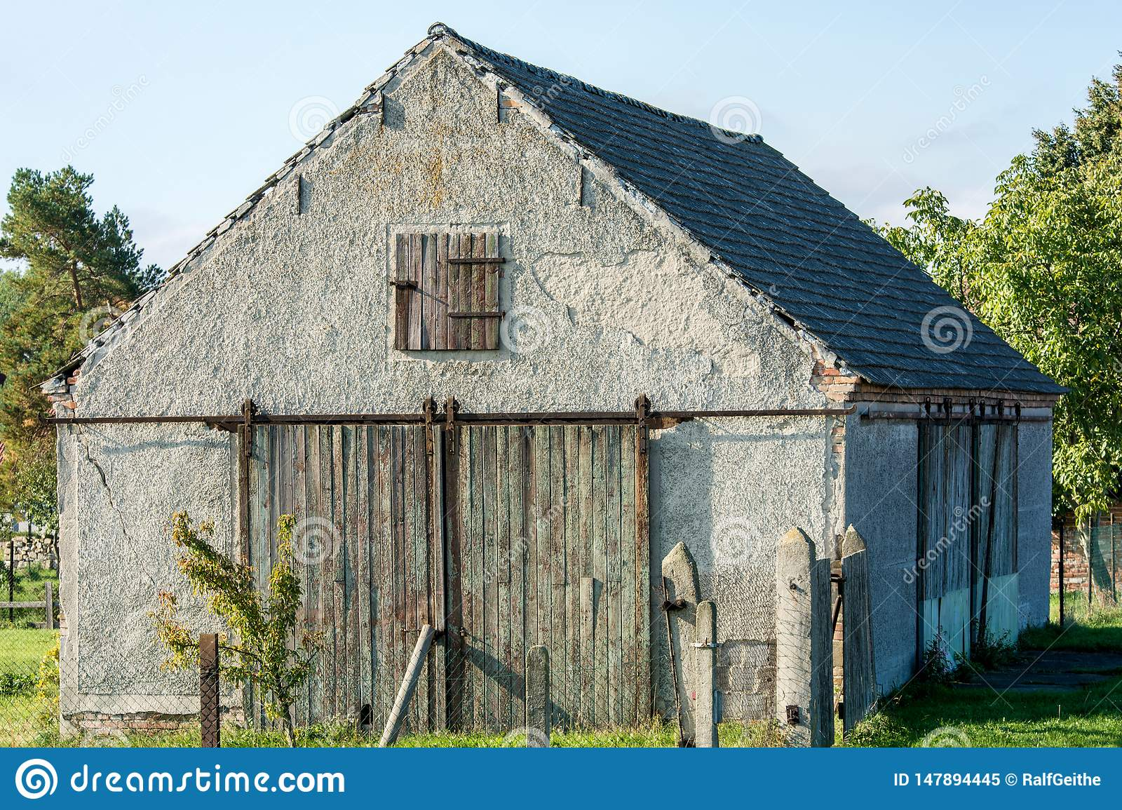 Wooden rolling door as a barn door on an old shed