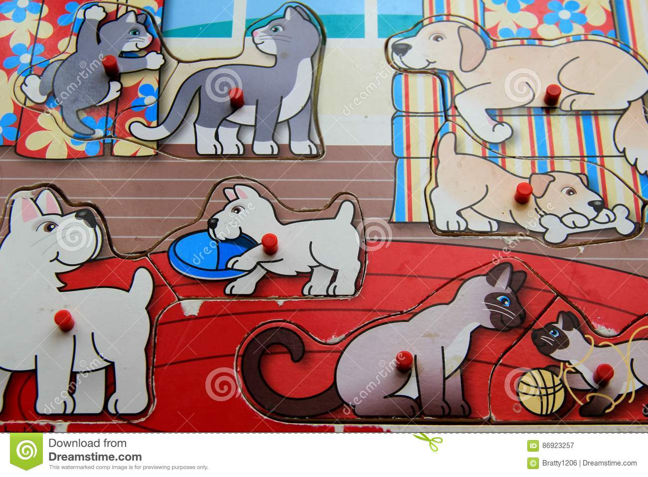 Old, beat - up child`s wood puzzle of playful pups and kittens