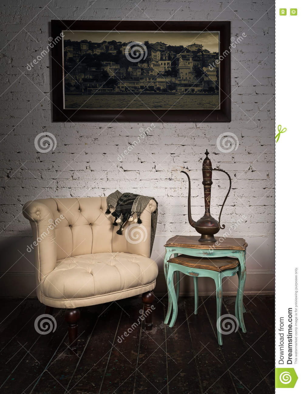 Old beige armchair, brass teapot, hanged painting and nested tables