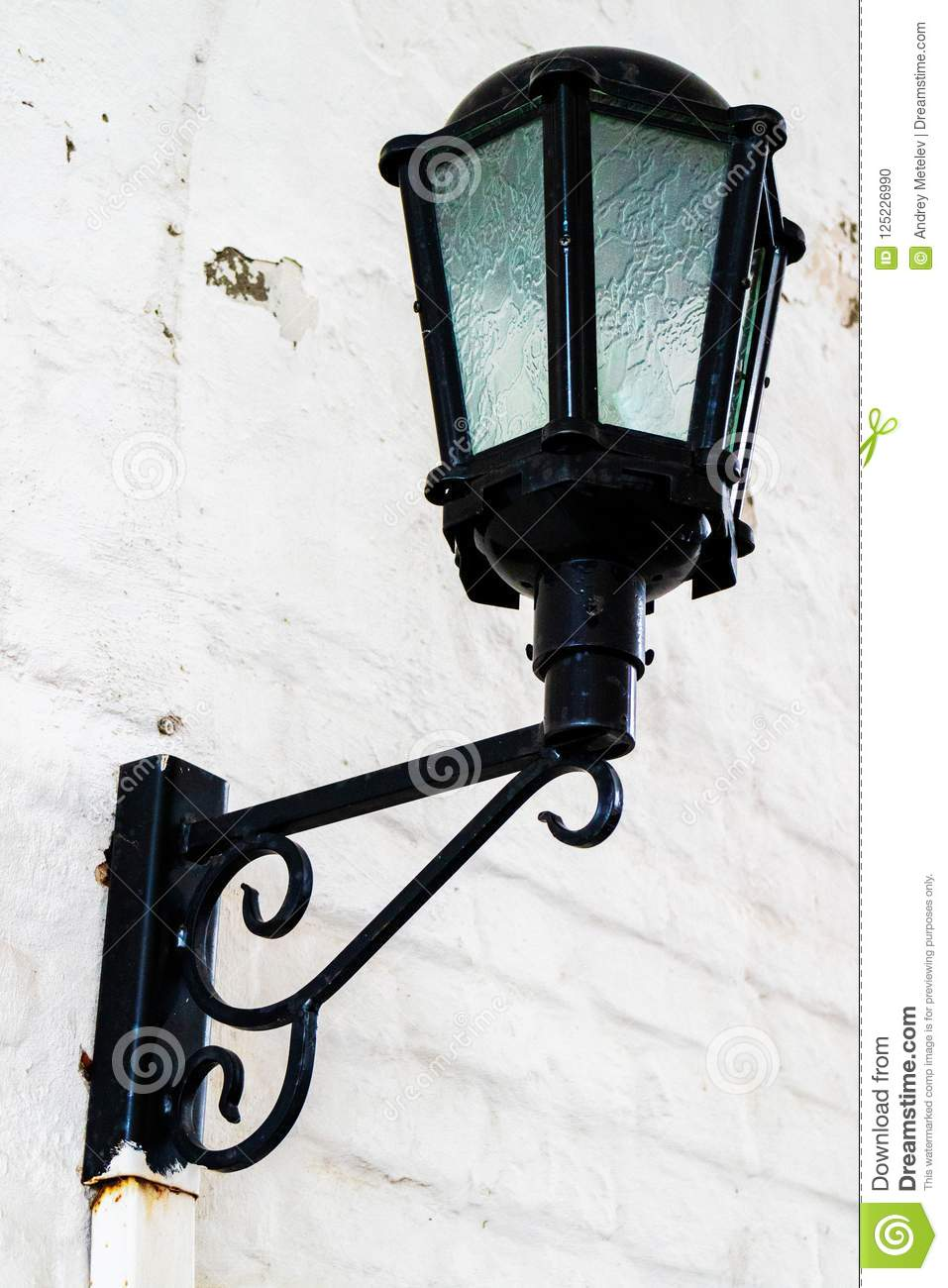 Old Black Cast Iron Lantern On A White Wall Stock Photo