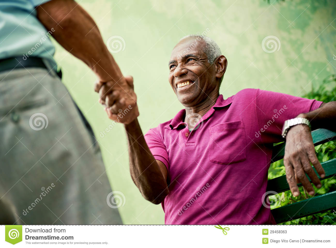 ... Photos: Old black and caucasian men meeting and shaking hands in park