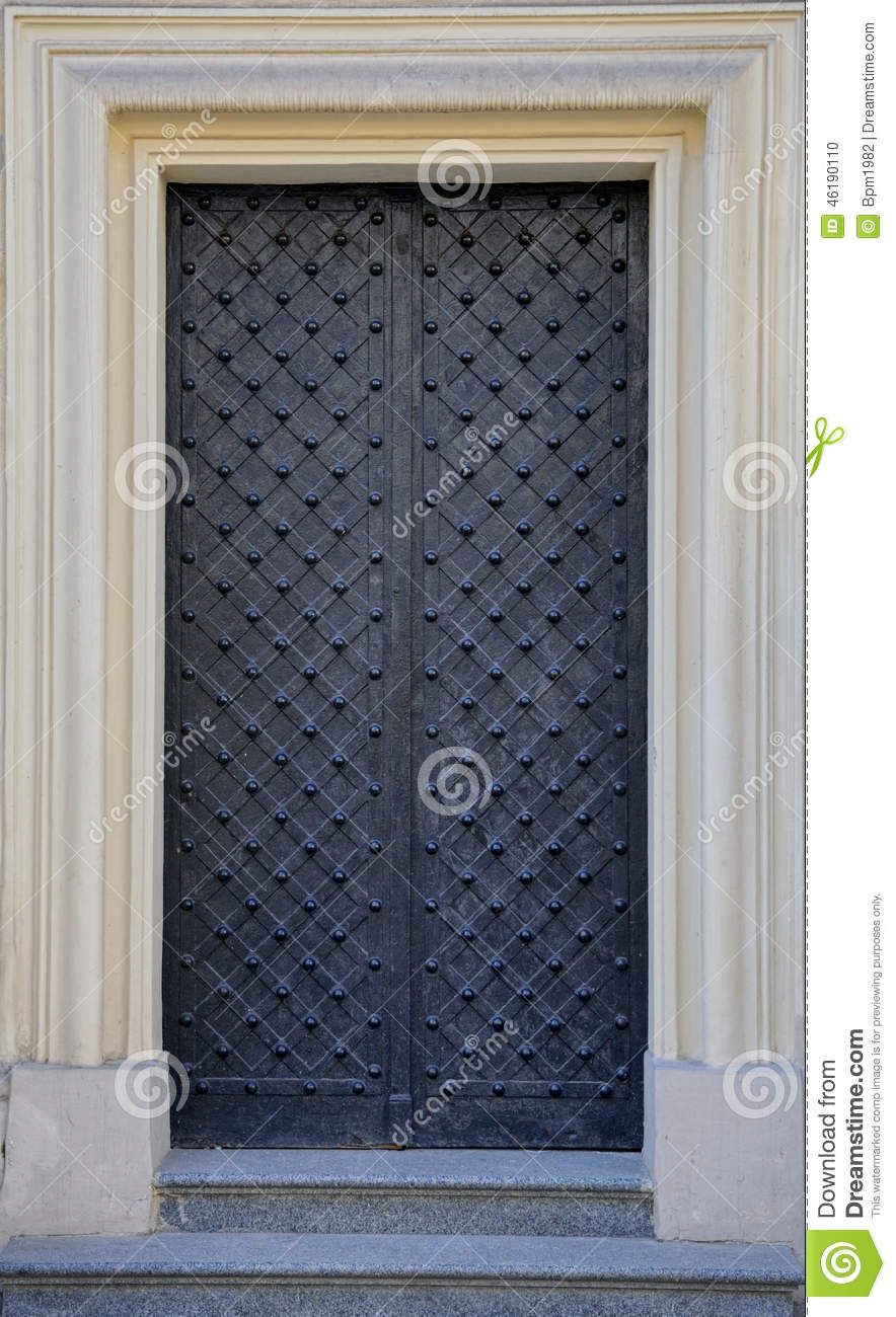 Black ancient metallic door in old stone wall stock image