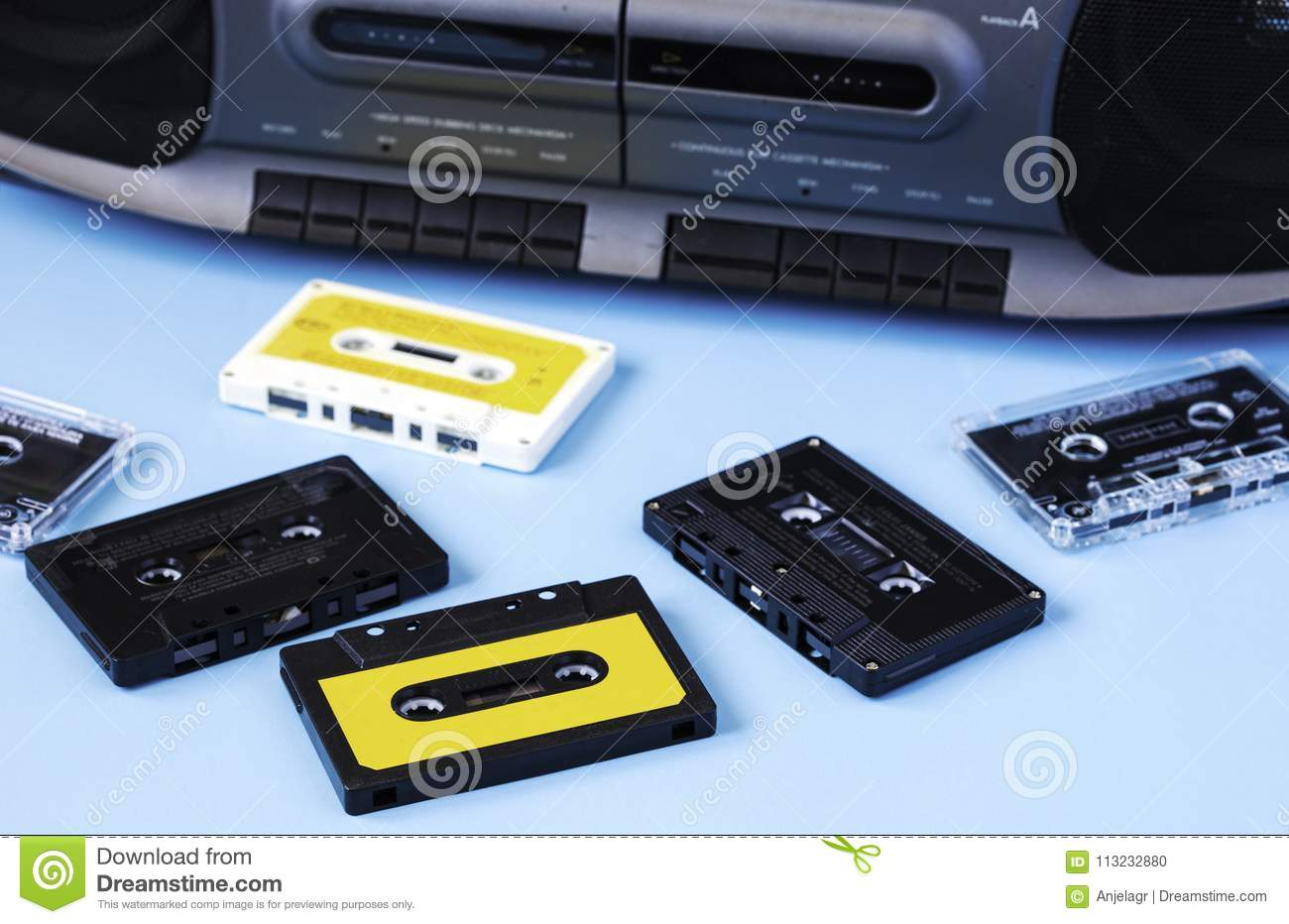 Old black retro cassette music audio tape recorder and retro cassette tape collection on blue background