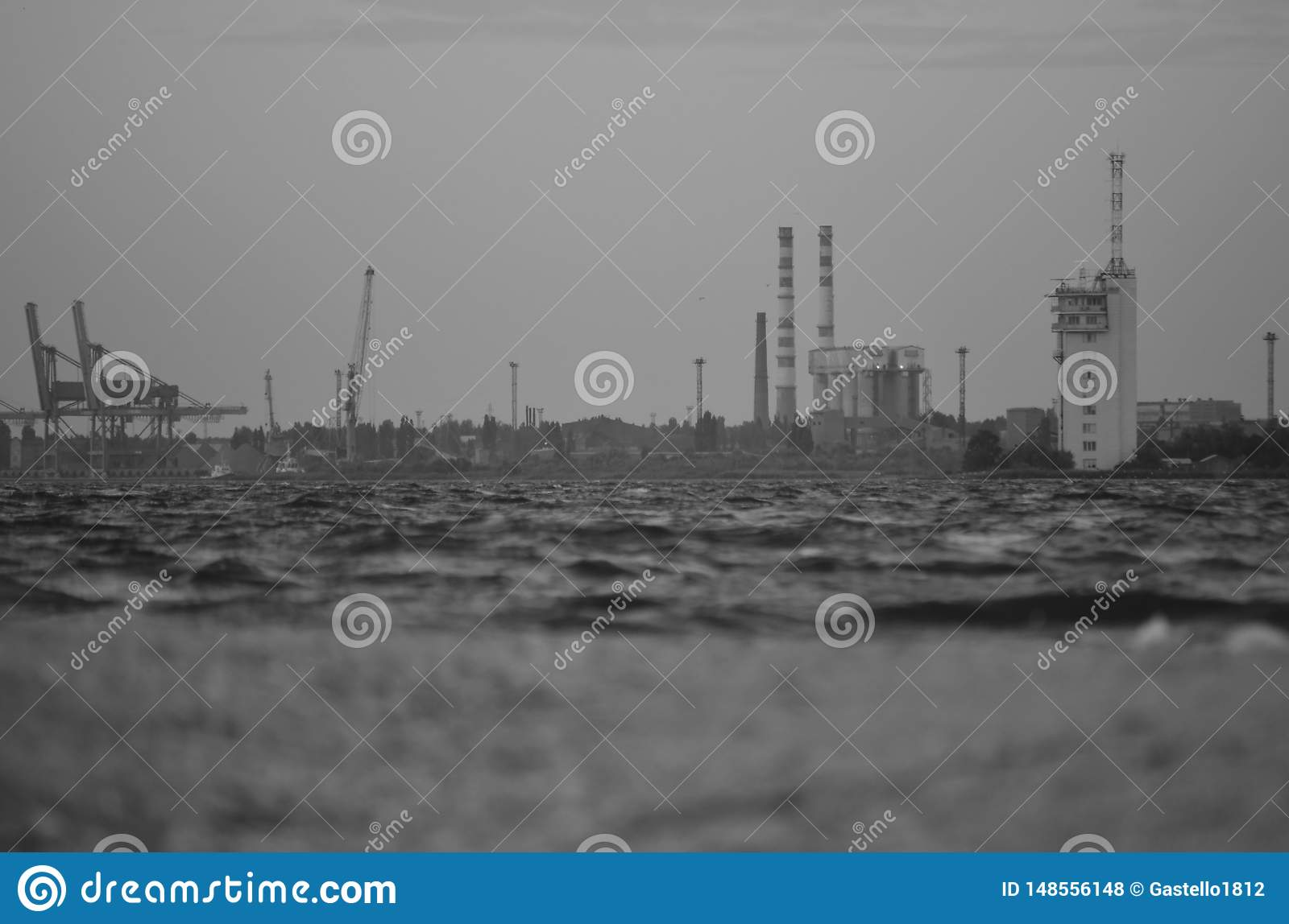 Vintage photo of the port and plant on the shore. View from the water to the shore. Monochrome