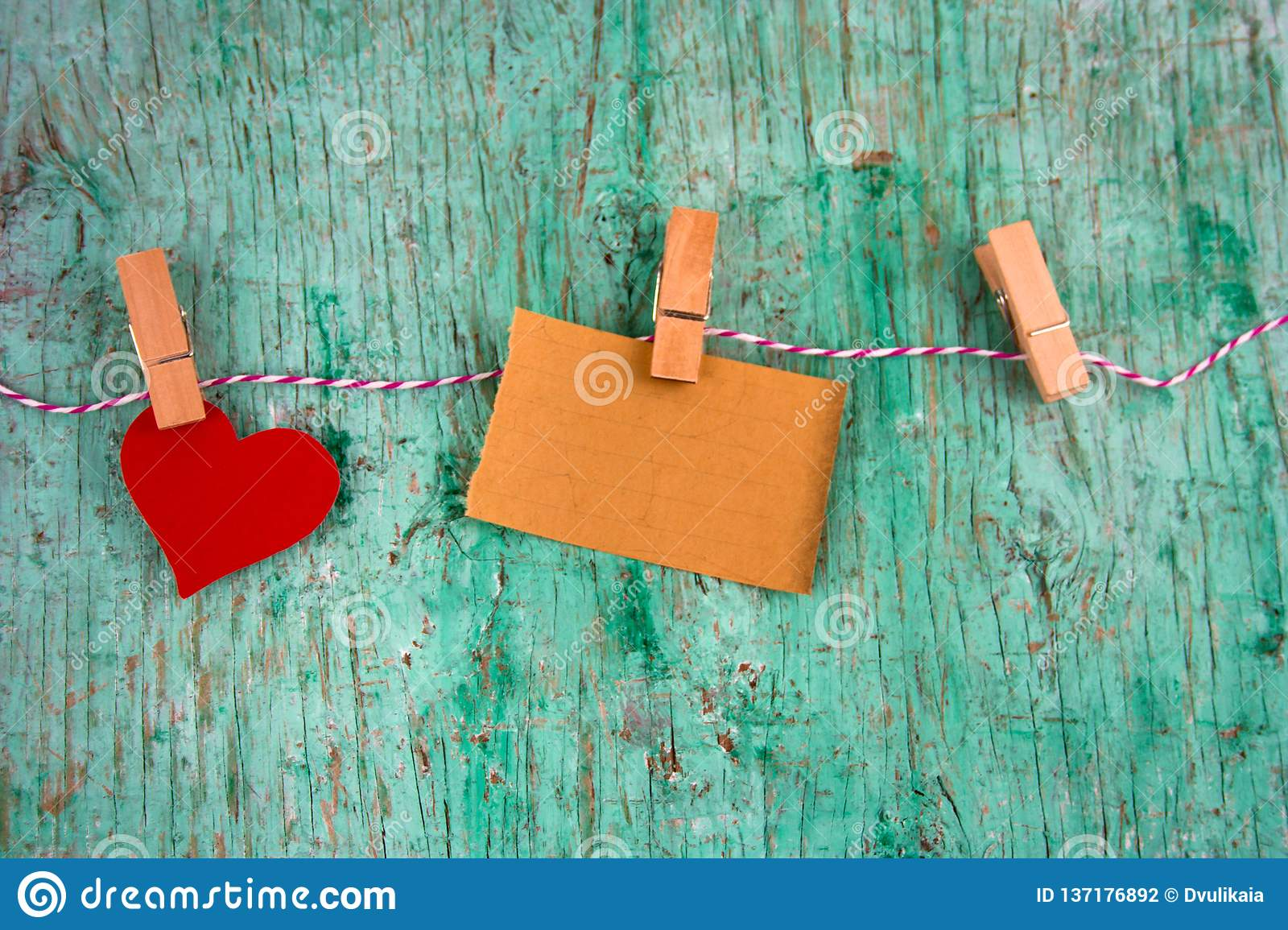 Old blank paper and paper red heart hung on clothespins