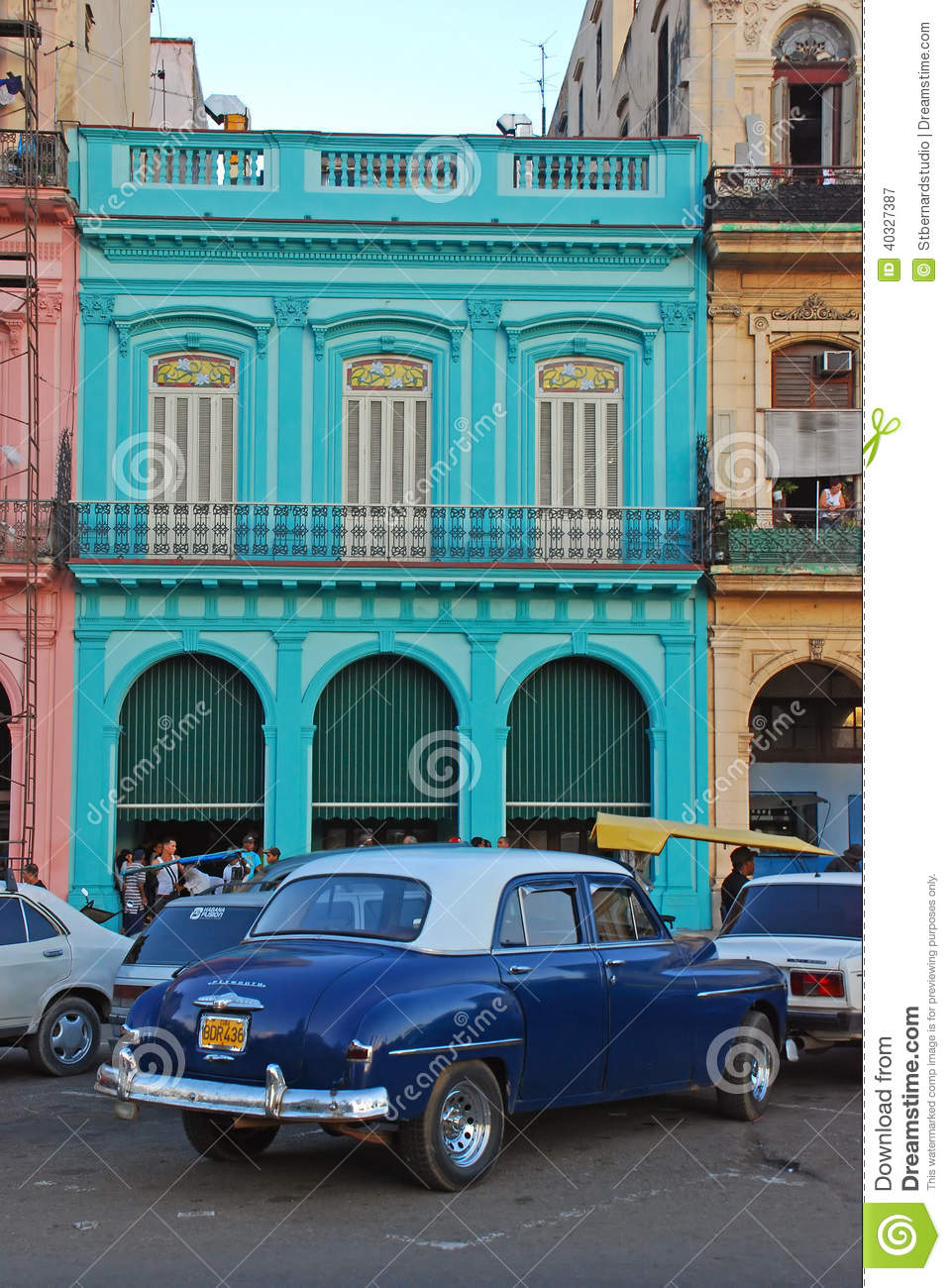 Old Blue Plymouth Car In Front Of Colourful Building In
