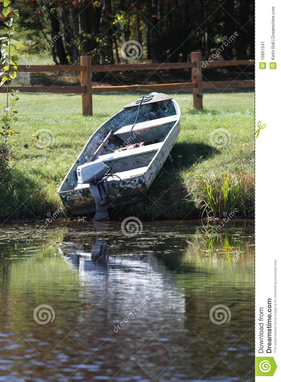 An Old Boat And Motor On The Shore Of A Lake Stock Image