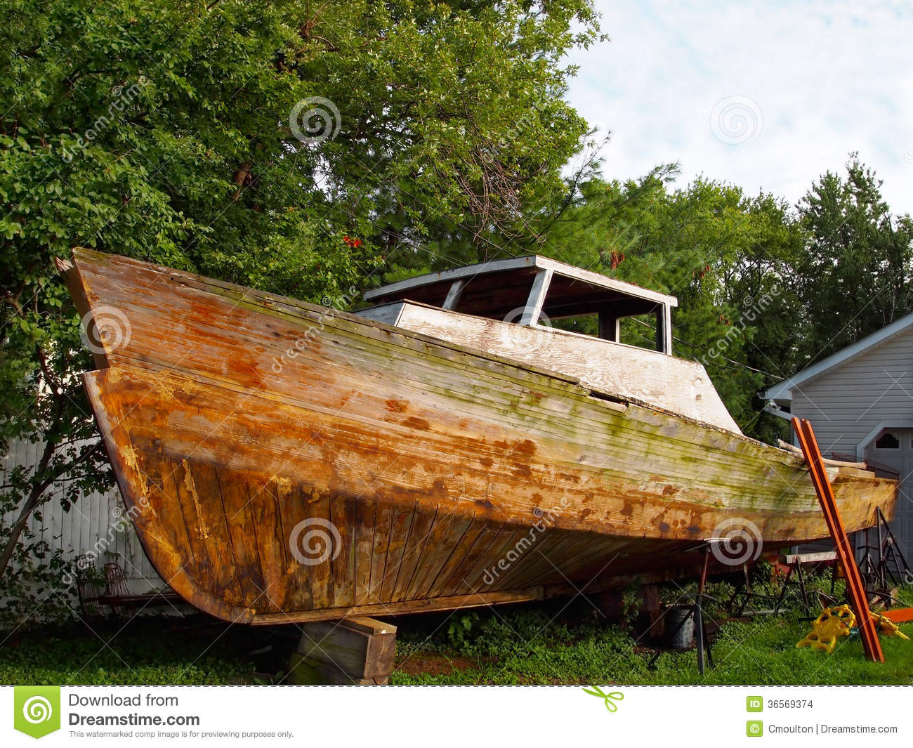 run down vintage wooden boat propped up on blocks on dry land being ...