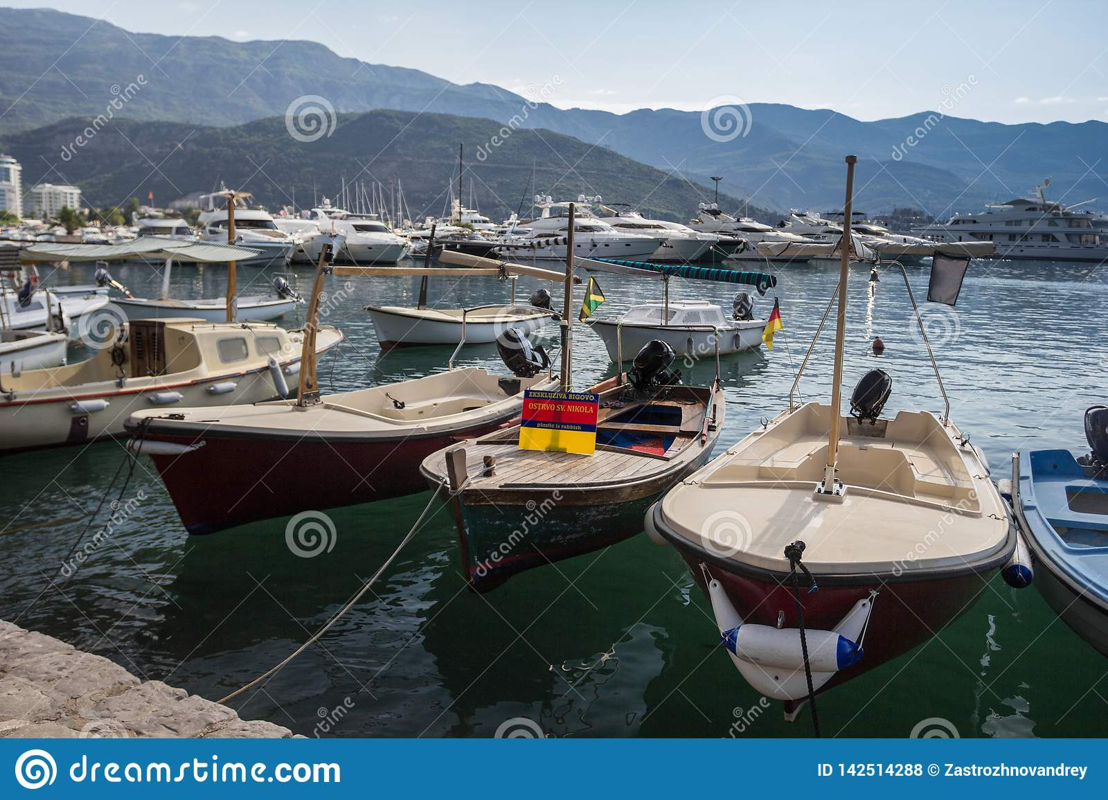Old boats at the pier on the background of mountains and yachts