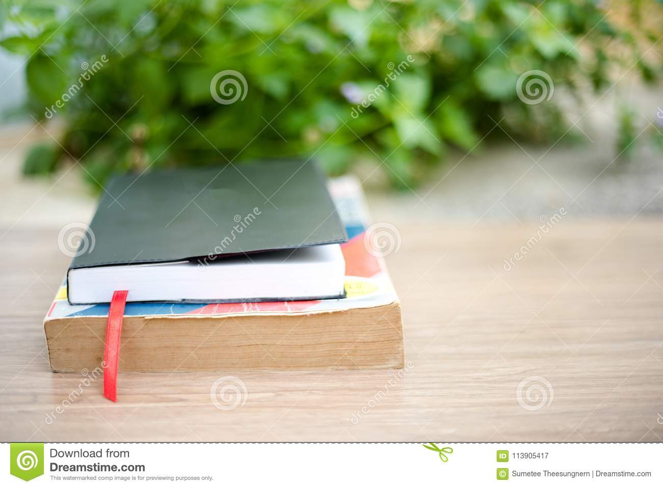 Old book on wooden table at home garden with nature bokeh backg