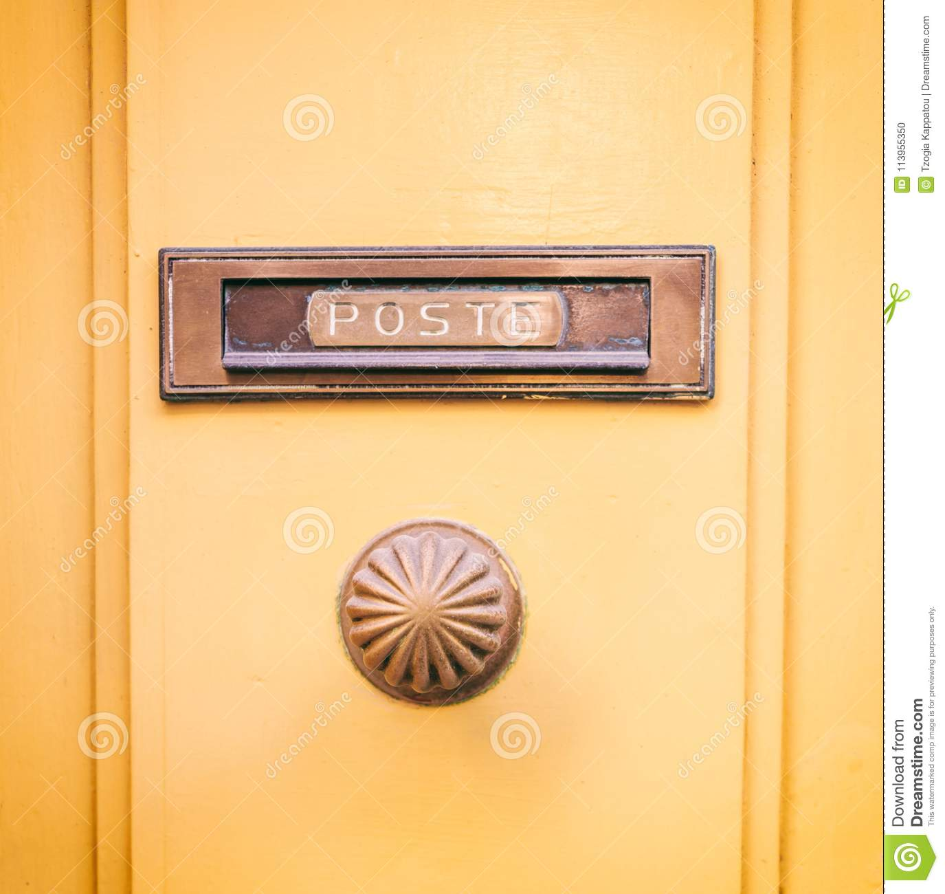 Old brass mail letter box and knob on a yellow painted front door, text poste