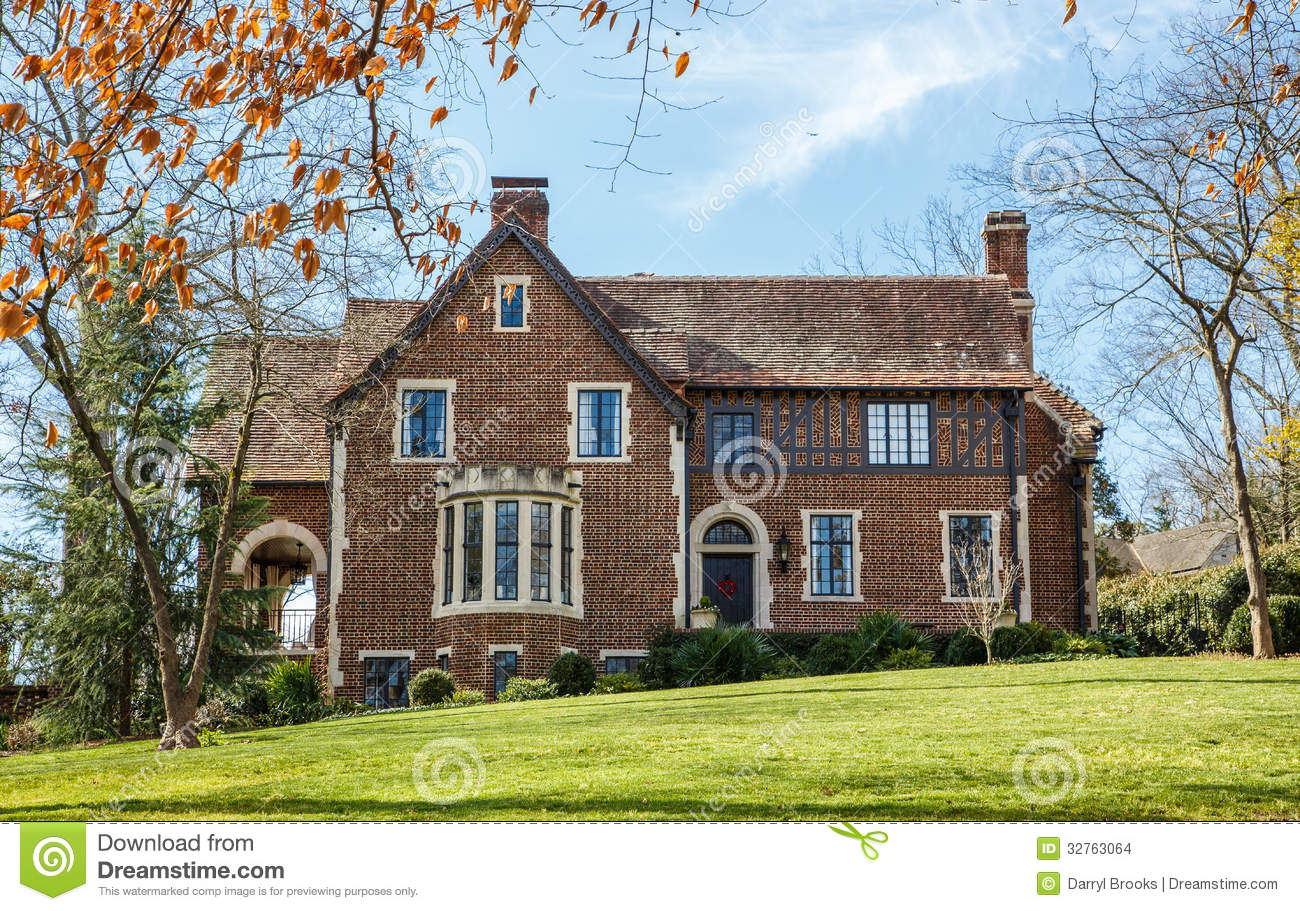 Old brick house with classic windows on green grass stock for Old house classics