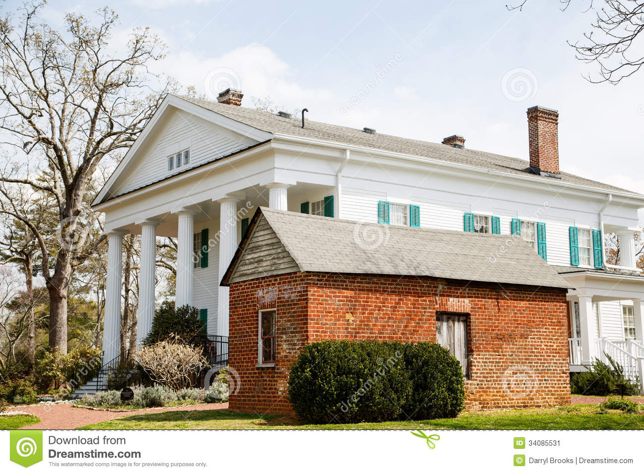 Old brick shed by white colonial home stock image image for Colonial porch columns