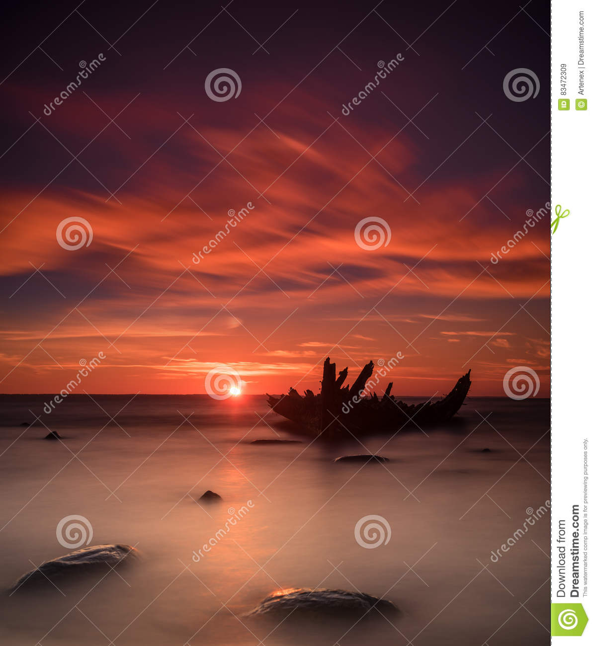 Old broken boat wreck on the shore, a frozen sea and beautiful blue sunset background.