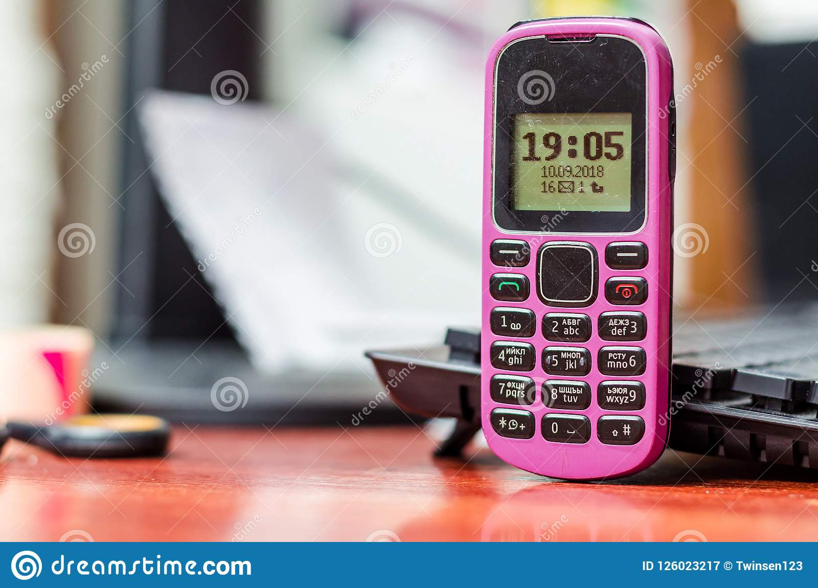 old button mobile phone pink color on the desk near a computer k