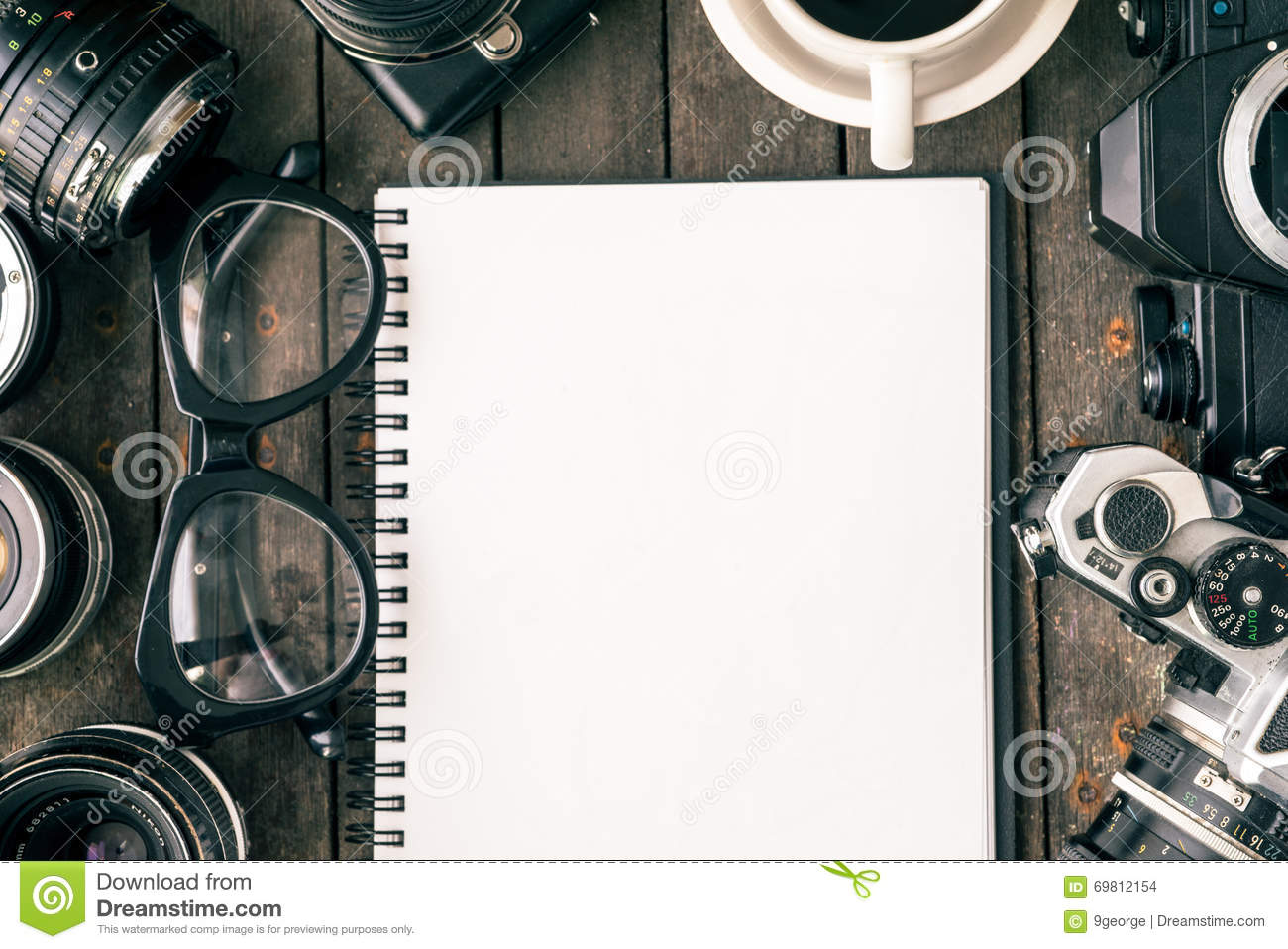 old cameras and blank paper on wooden table top view stock photo
