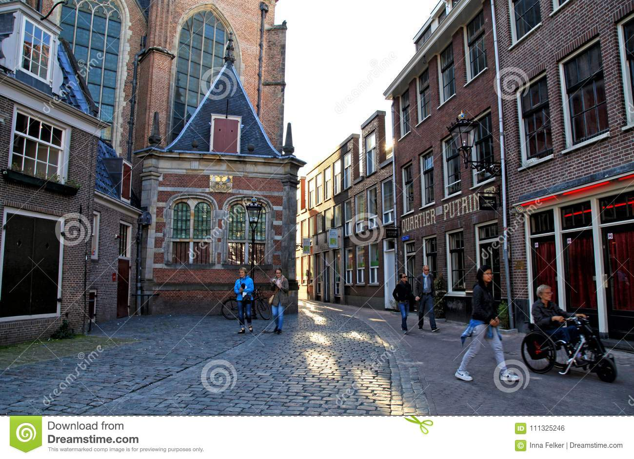 Old church and tourists on the street at the red light district