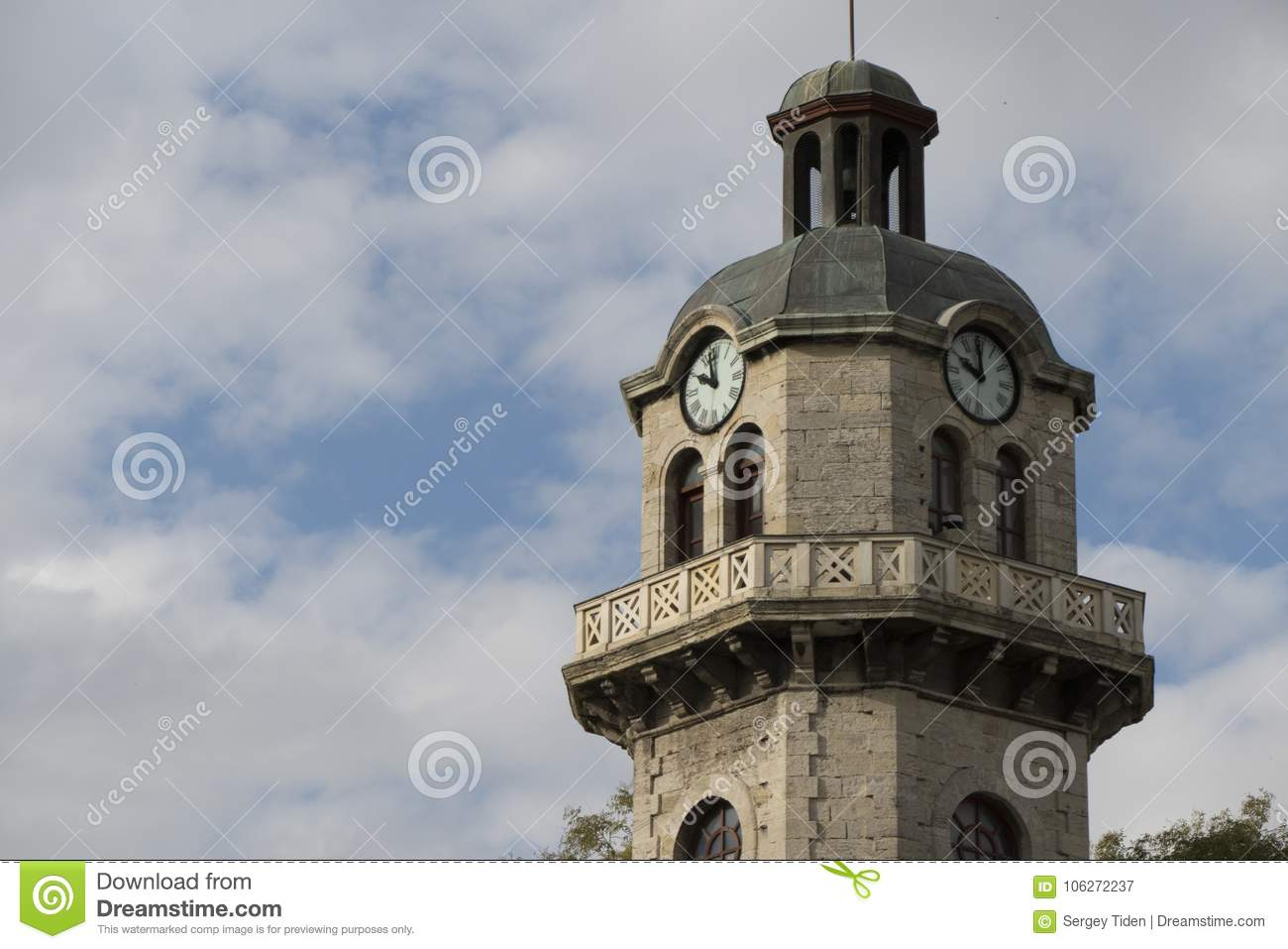 Old city clock tower on a cloudy sky background