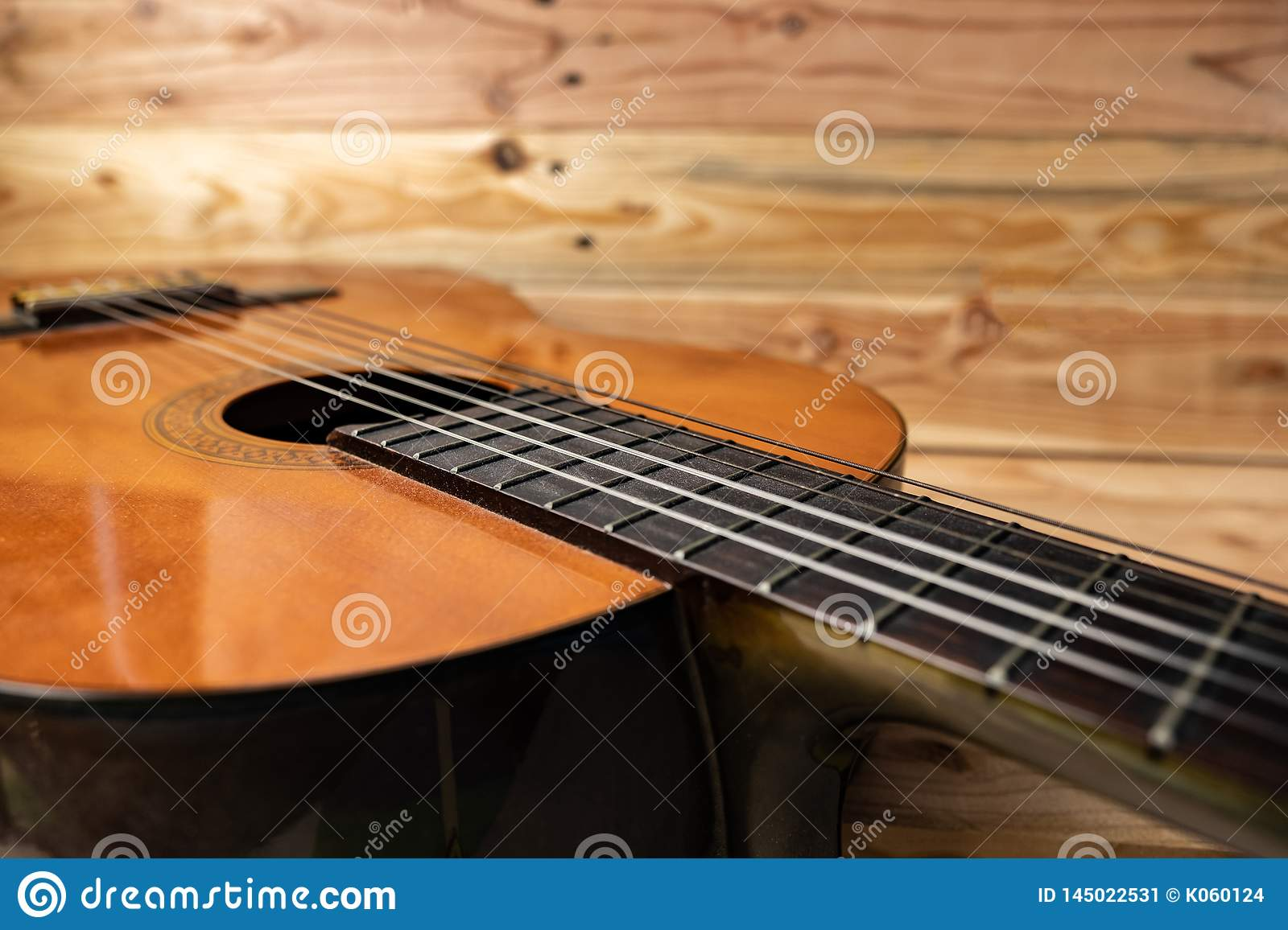 Old classical guitar on wooden background