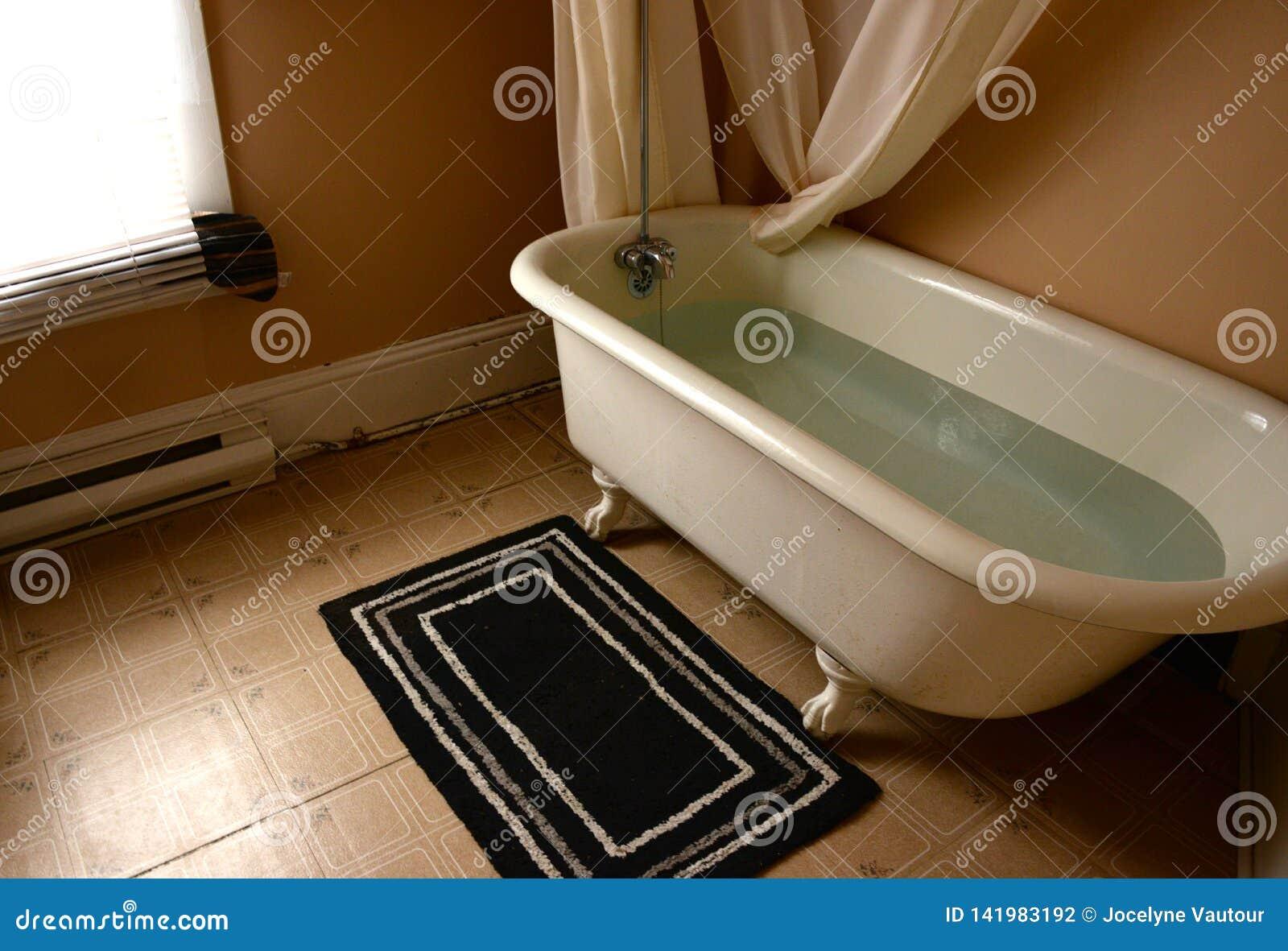 Old claw foot bathtub in old bathroom