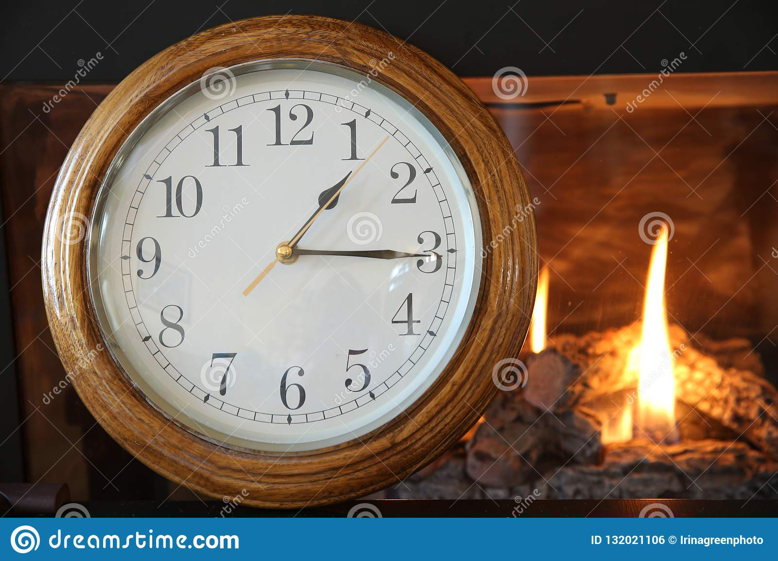 Clock on the background of a burning fire in the fireplace