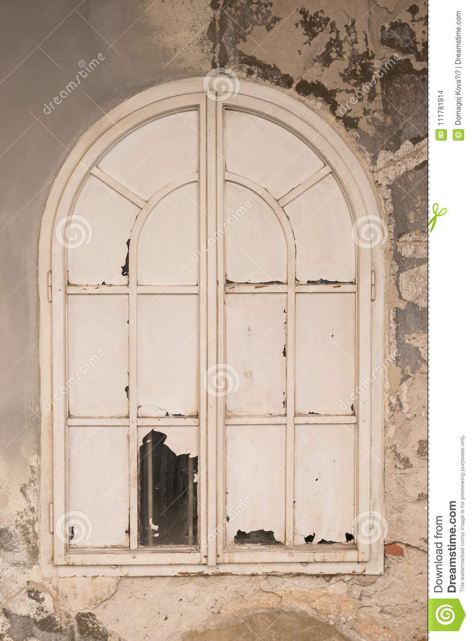 Old and closed white window on ruined wall.