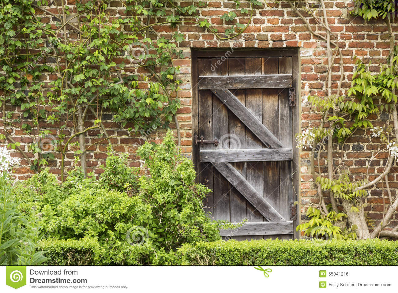 Old Closed Wooden Door In A Brick Wall In A Garden Stock