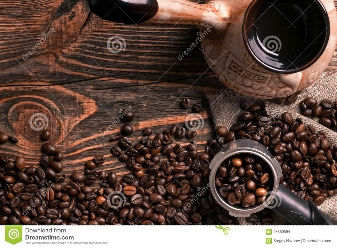Old coffee cup and turk with roasted beans on a wooden table.