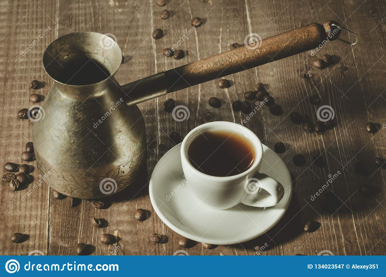 Old coffee pot, hot cup and coffee beans on dark rustic background/Old coffee pot, hot cup and coffee beans on dark rustic