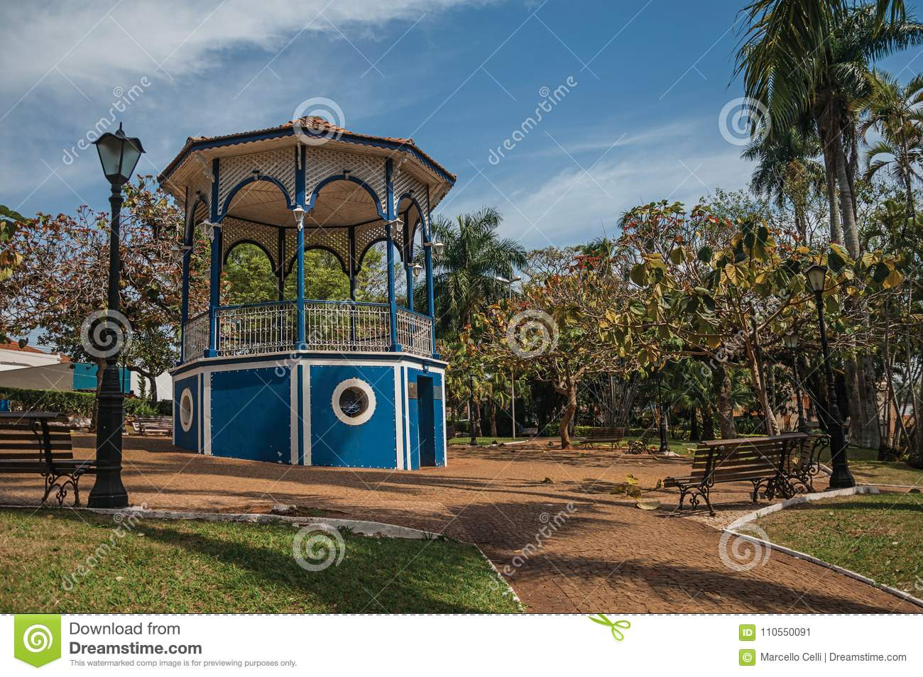 Old colorful gazebo and lighting pole in the middle of verdant garden full of trees, in a sunny day at São Manuel.