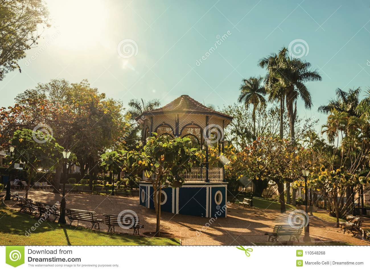 Old and colorful gazebo of square in the middle of verdant garden full of trees, in a bright sunny day at São Manuel.