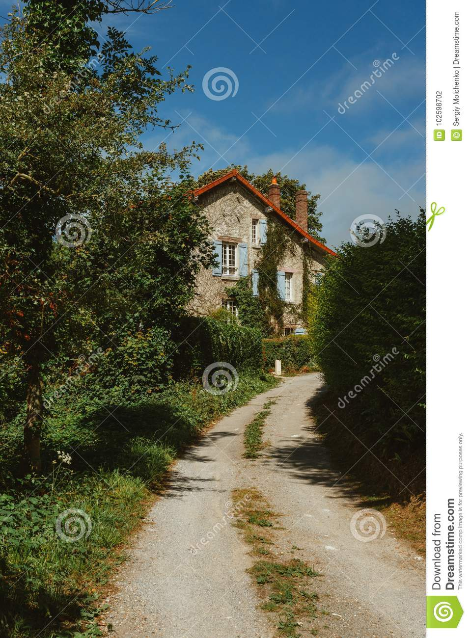 Old Country House With Blue Shutters And Gravel Road In