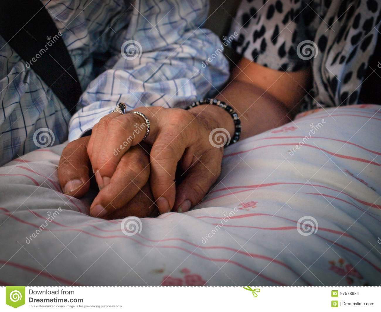 Old couple holding each other hands