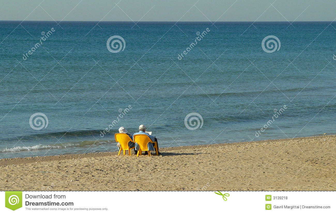 Old Couple relaxing by the sea