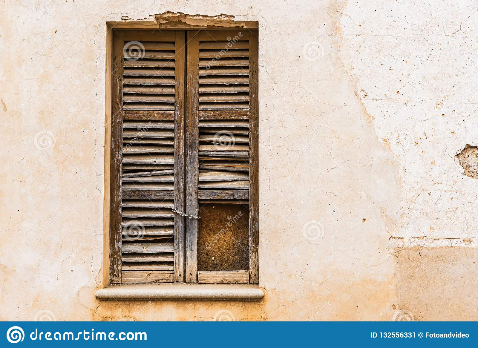 Ancient Broken Wooden Window Shutter With Rustic Stucco Wall