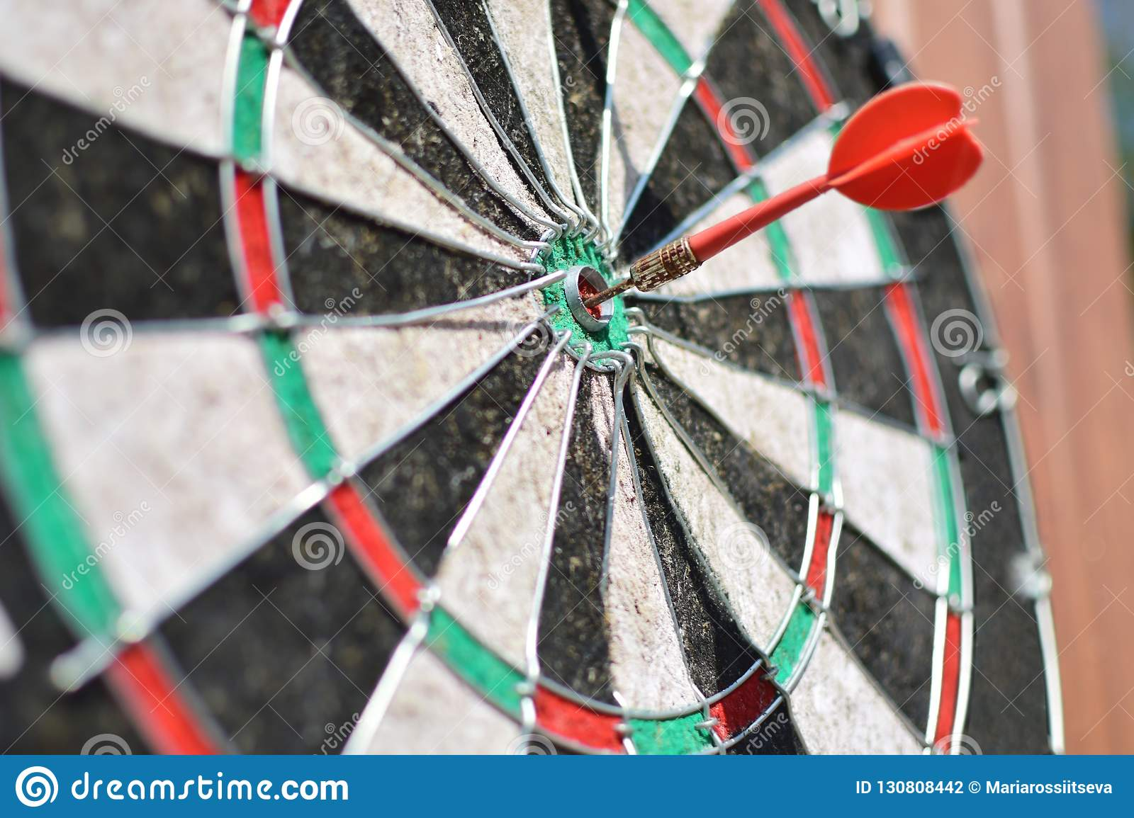 Old dart board with arrow hitting a target.
