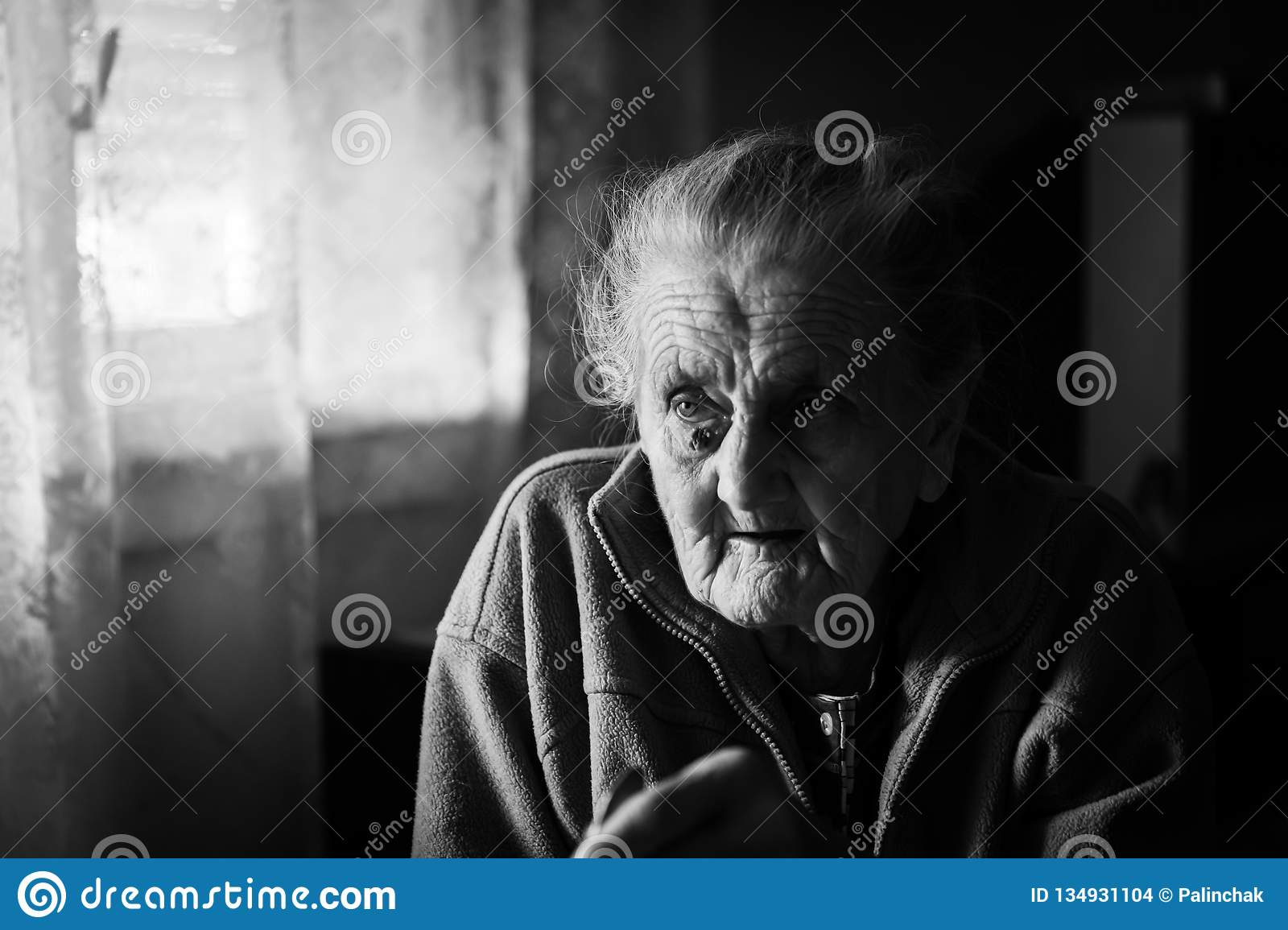 Black and white image of an old depressed woman an elderly lonely woman sits at a table in the kitchen near the window and drinking tea