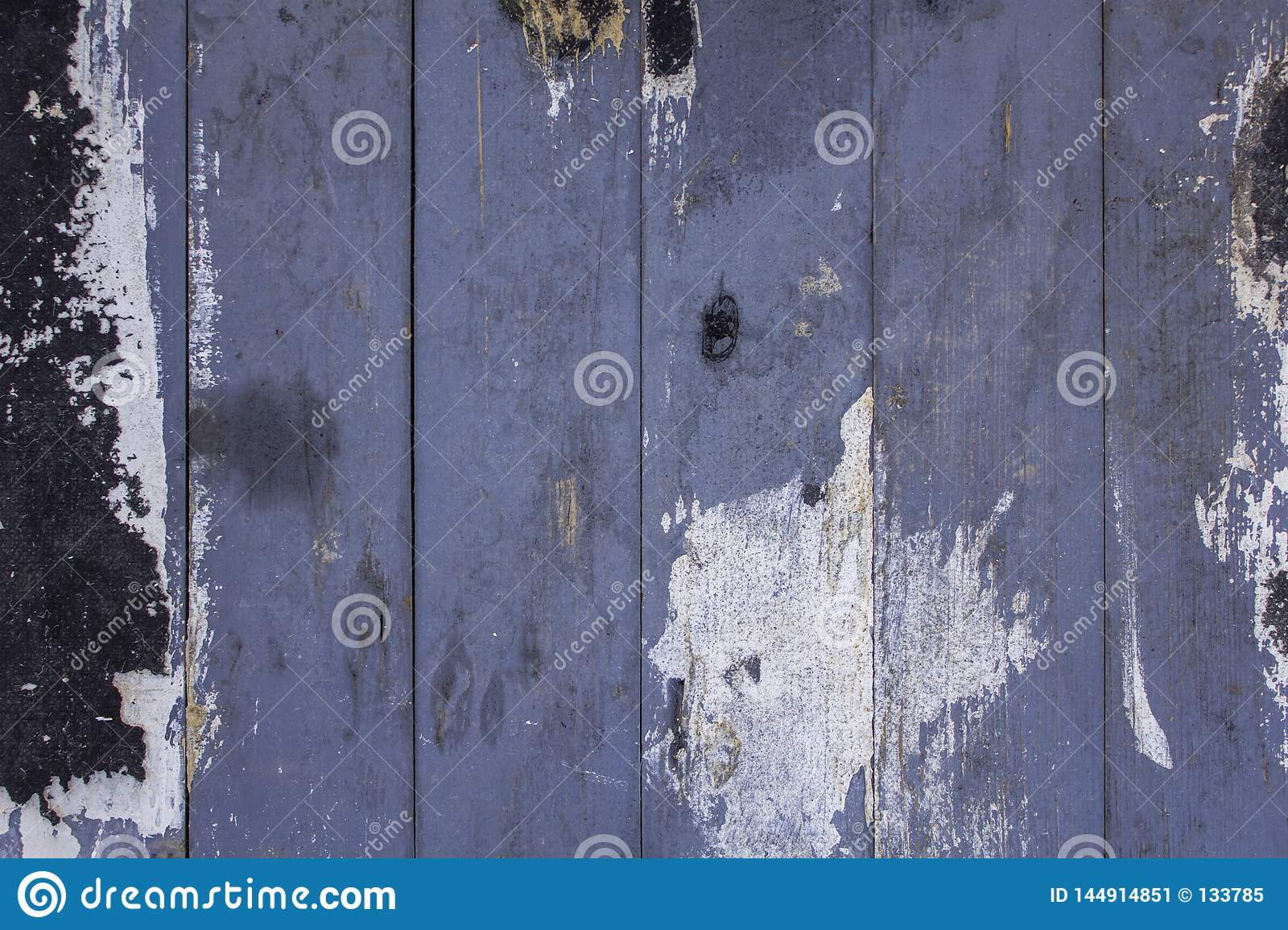 Old dirty blue gray fence from wooden boards with scratches and stains of black white paint. vertical lines. rough surface texture