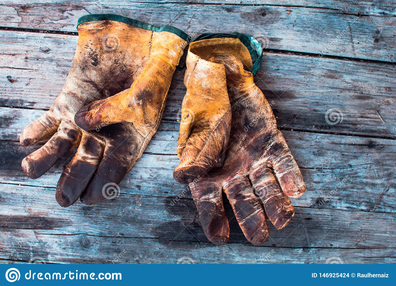 Old and dirty working gloves over wooden table,  gloves for each finger