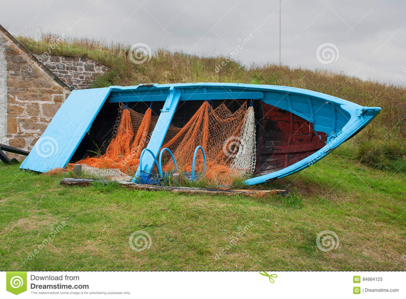Old disused timber built fishing boat with nets and lobster pots on display