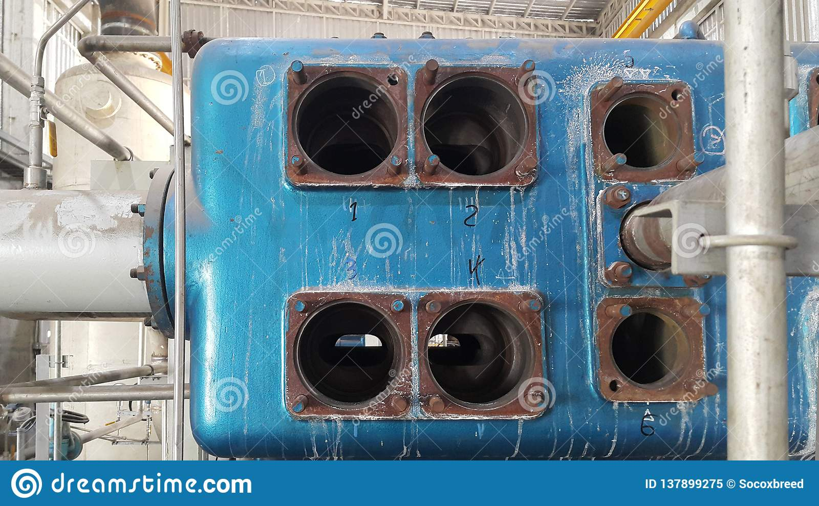 Old electrical motor with blue vacuum and blowers inside old factory