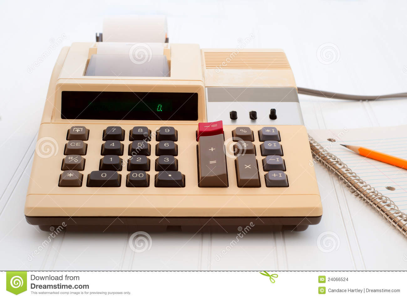 An old electric calculator on a white bead board surface with a pad of