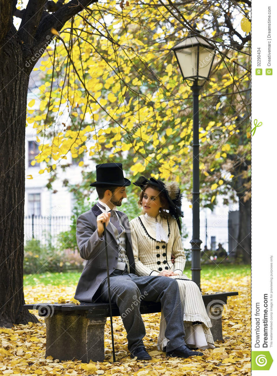 Old Fashioned Dressed Couple On A Park Bench In Fall Stock Photo