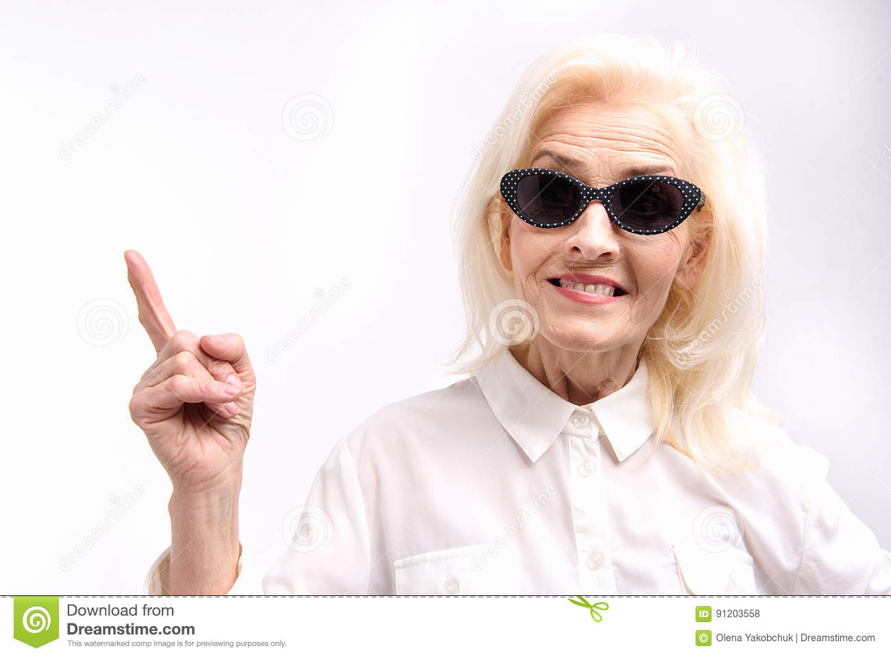 205ac466eca Mature lady in sunglasses is looking at camera with bright smile and pointing  up. Portrait. Isolated. Copy space on left side