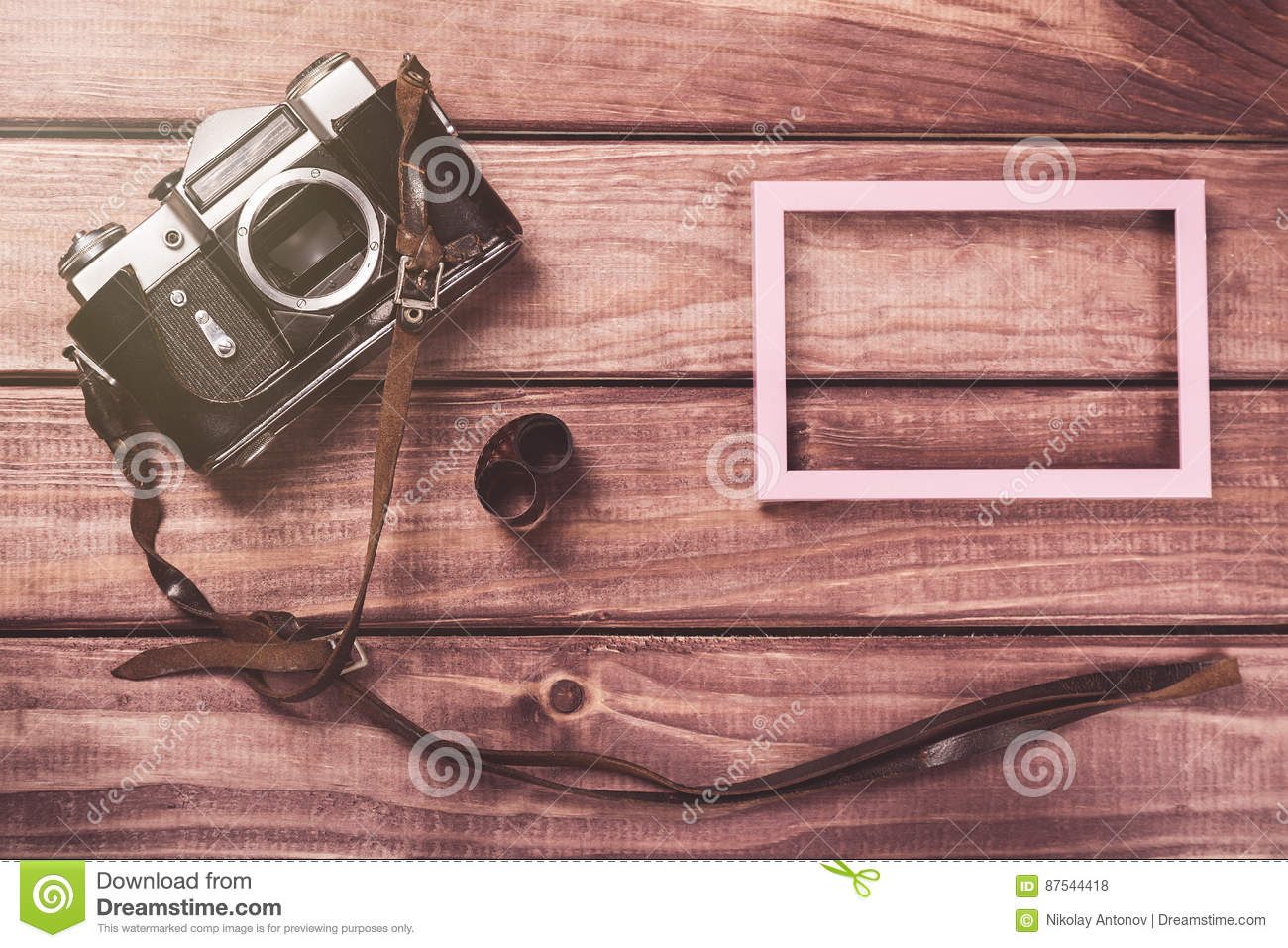 Old film camera with strap, photo frame and film on wooden background. Vintage toned and top view